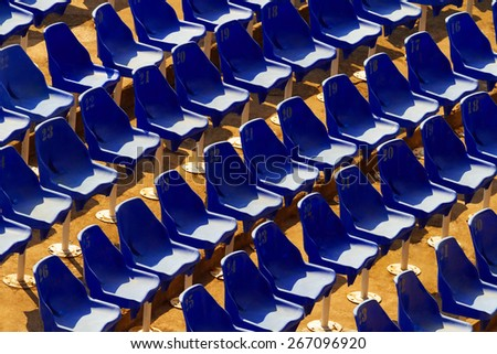 Chairs on abandoned stadium A few rows of old plastic chairs - stock photo