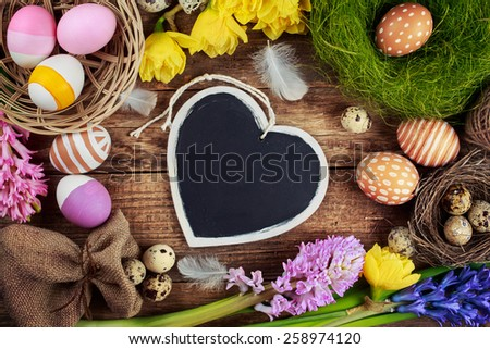 Chalk board in the shape of hearts and Easter decorations, eggs, flowers - stock photo