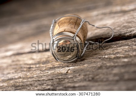 2016 champagne cork lying on a rustic wooden table in a New Year background, tilted angle with shallow DOF and copyspace. - stock photo