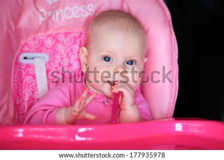 cheerful baby child eats itself with a spoon - stock photo