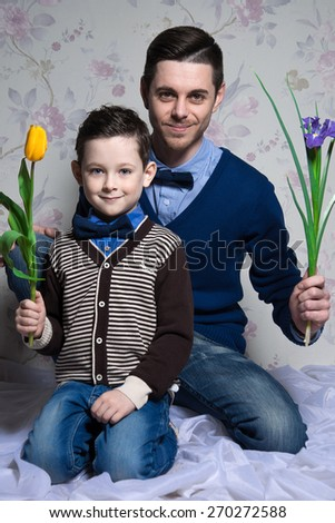 Cheerful father and son are sitting close to each other. Isolated on floral background. Hold flowers in their hands. Studio shot - stock photo