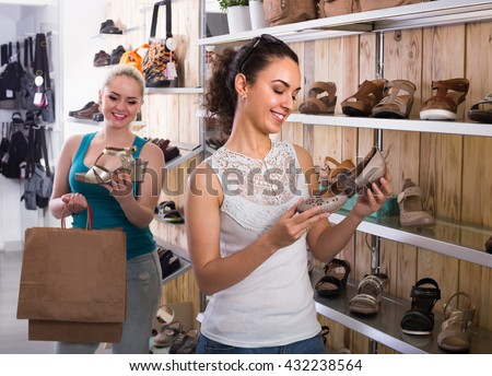 cheerful girl showing a chosen pair of shoes while her friend still choosing - stock photo