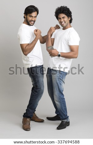 Cheerful happy two young men using smartphone over grey background - stock photo