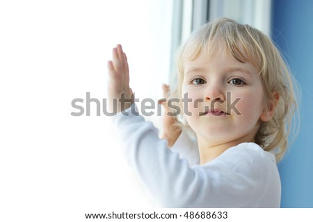 cheerful little girl sits at  window