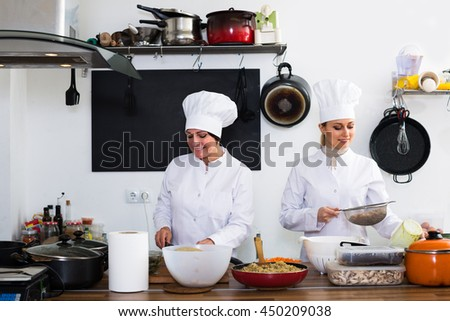Cheerful mature and young women cook wearing in white uniform standing on kitchen - stock photo