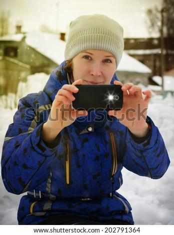 Cheerful woman using phone camera. - stock photo