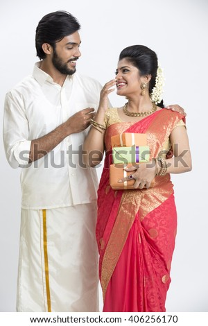 Cheerful young south Indian couple holding gift boxes on white background, Festival concept.  - stock photo