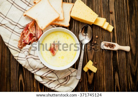 cheese soup with smoked pork ribs , potatoes, carrots , peppers , spices and bread on the wooden background - stock photo