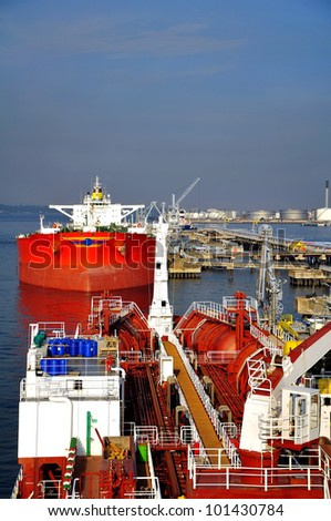 chemical tanker on the background of crude-oil tanker in port - stock photo