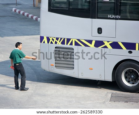 CHIANG MAI, THAILAND - FEBRUARY 28 2015: Man give signs for bus Reverse out of terminal. Bus of Greenbus Company. Photo at New Chiangmai bus station, thailand. - stock photo