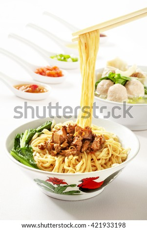 chicken noodles, favourite meals in south east asia. served in legendary bowl and a delicious meatball at the background  - stock photo