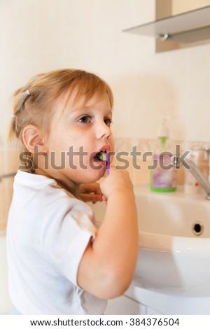 child cleaning   teeth by   sink in bathroom.