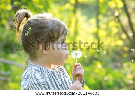 child girl blowing soap bubbles outdoor at sunset