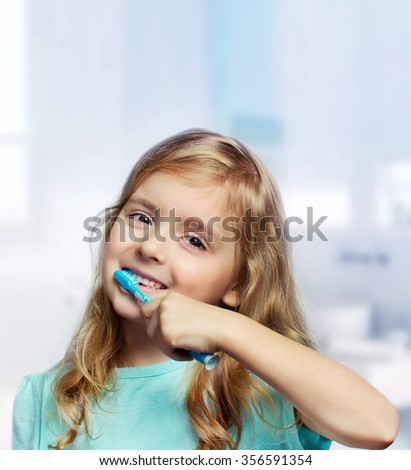 Child girl closeup cleaning teeth in bathroom. Caucasian happy smiling kid brush teeth. - stock photo