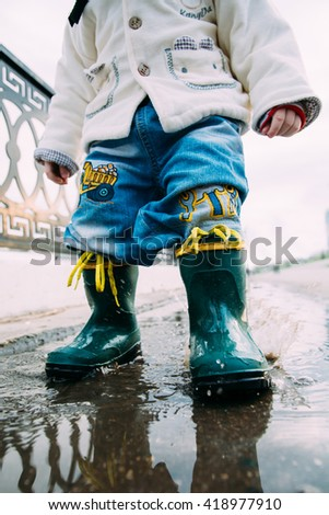 child walks through the puddles in rubber boots