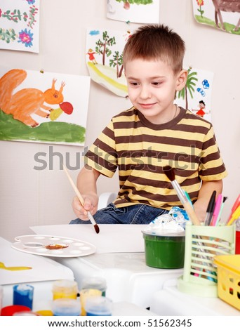 Child with brush draw picture  in play room. Preschool.