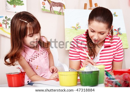 Child with teacher draw paints in play room. Preschool. - stock photo