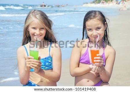 Children drinking juice on beach - stock photo