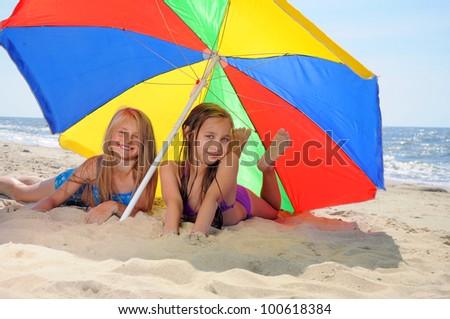 Children laying on beach - stock photo