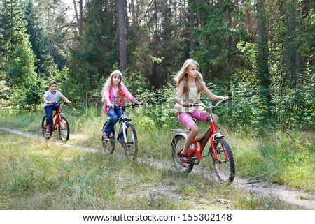 Children riding bikes in woods on sunny summer day