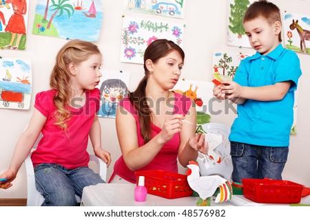 Children  with teacher  in play room. Preschooler. - stock photo