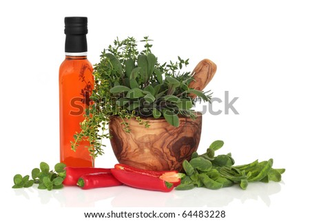 Chilli olive oil, chillies, and herb leaf sprigs of rosemary,  sage, thyme and oregano in an olive wood mortar with pestle, isolated over white background. - stock photo