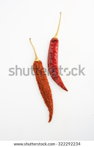 2 chillies, one chilli made up of chilli powder, isolated on white background, vertical orientation, indian spices - stock photo
