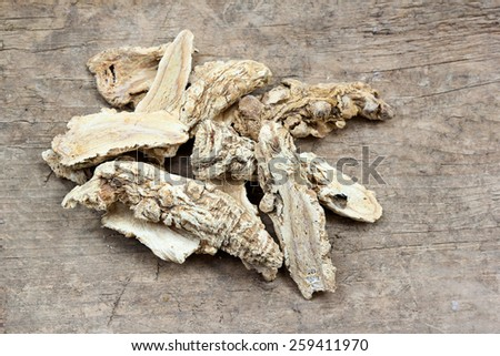 Chinese Herbal medicine - Dang Gui Ginseng (Angelica Sinensis) on wooden board - stock photo