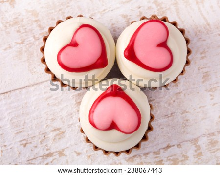 chocolate cupcakes with vanilla icing and a red heart