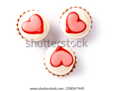 chocolate cupcakes with vanilla icing and a red heart isolated on white background