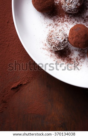 Chocolate sweets with cocoa and coconut chips on a white plate, top view, selective focus - stock photo