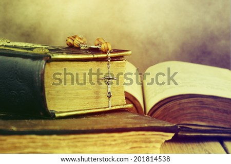 Christian cross necklace next to holy Bible. - stock photo