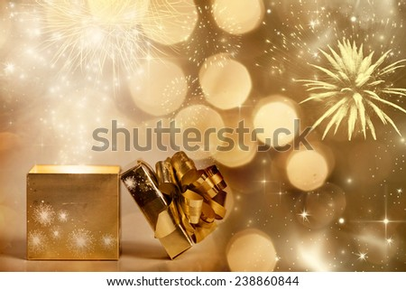 Christmas background with gift box over sparkling background and fireworks - stock photo