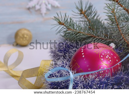 Christmas .Christmas toys red ball surrounded by fir tree branches, and a Golden ribbon light blue background blur snowflake - stock photo