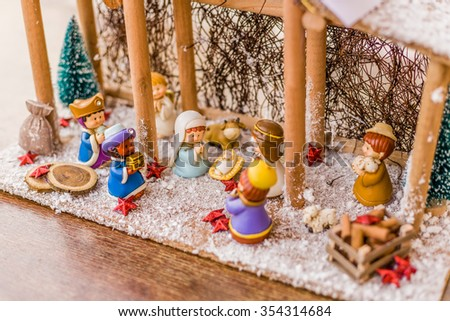 Christmas Nativity scene, the Blessed Virgin Mary and Saint Joseph watch over the Holy Child Jesus in a manger as the ox and the donkey are warming and while three wise men are bearing gifts - stock photo