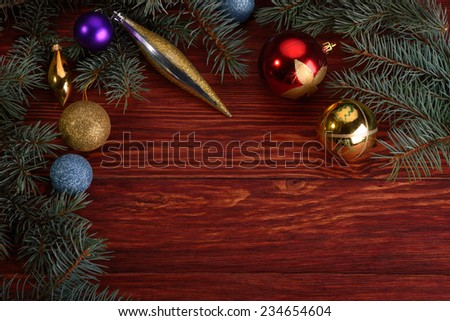 Christmas toys of different colors with fir tree branches on wooden table
