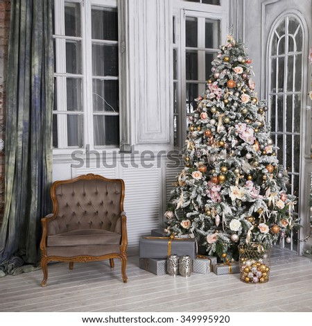 Christmas tree on wooden floor in white interior. Christmas tree decorates with artificial flowers, garlands and Christmas toys - stock photo