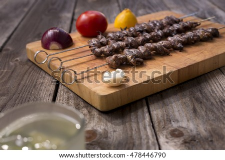"""Churrasco de curacao"",traditional Brazilian barbecue food, grilled chicken hearts composition with tomatoes and onion salad an old wooden table."