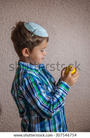 Citrus -  ritual fruit for the Jewish holiday of Sukkot. Beautiful seven year old boy in white knitted skullcap is holding citrus - stock photo
