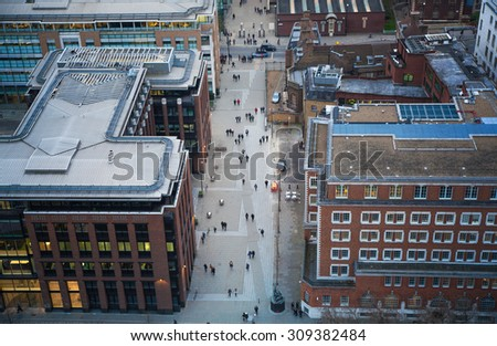 City of London panorama in dusk. Millennium foot bridge over the River Thames and office people walking through the streets - stock photo