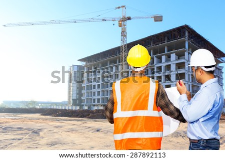 Civil engineer and foreman control working at building construction site