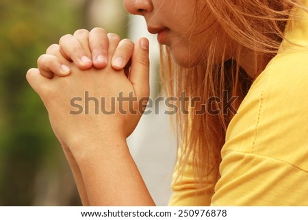 Clasped hands of woman in garden  - stock photo