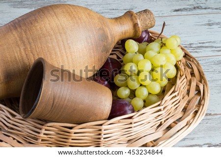 Clay bottle with wine, glass, grapes and plums in a wicker basket on a light wooden table.
