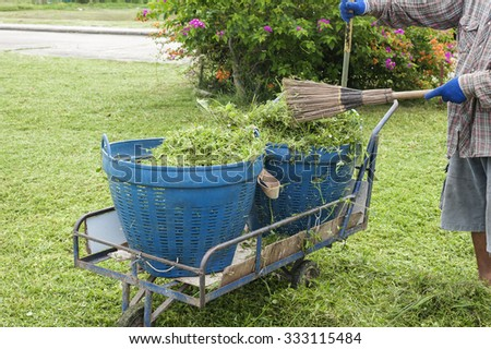 cleaning the lawn and raking up grass clippings after mowing with a pile of grass and rake leaning on a plastic bin - stock photo