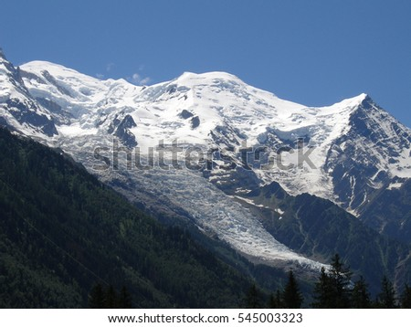 Clear blue sky above the white peaks of the Mont Blanc massif and Les Bossons glacier.