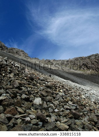Climber on scree                               - stock photo