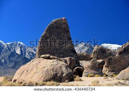 climber on sharks fin arete route with mount whitney in background at alabama hills , california - stock photo