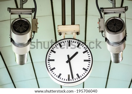 Clock with loundspeakers on sky train station ,at BTS Banhkok inThailand. white roof background - stock photo