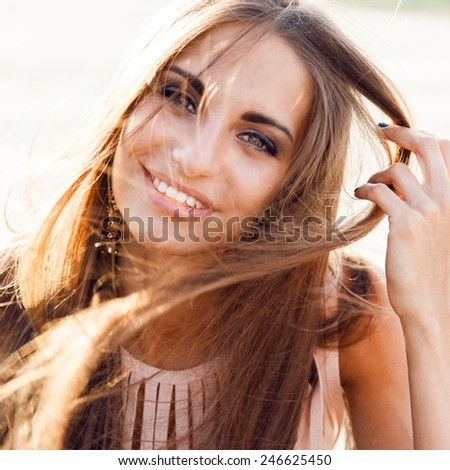 Close up fashion portrait of a beautiful girl in evening dress with windy long hair on the face. She smiling and having fun in the rays of the setting sun. - stock photo