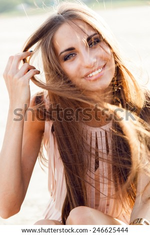 Close up fashion portrait of a beautiful woman with big eyes and full lips and white teeth  in evening dress with windy long hair . She smiling and having fun in the rays of the setting sun. - stock photo